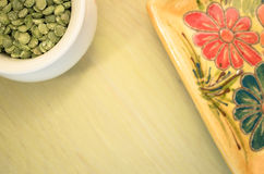 Yellow porcelain tablemat and dried pease on a pastel green back Stock Photos