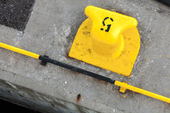 Yellow port mooring bollard with number 5 label Stock Photos