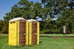 Yellow portable toilets. Two yellow portable toilets at a park royalty free stock photo