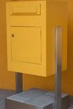 Yellow post box stands on concrete base. Big yellow mailbox on concrete base before yellow house stock images