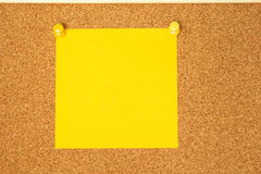 Yellow post-it on a coarkboard background Stock Images