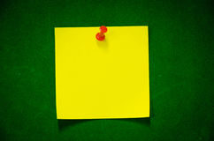 The yellow Post it. Post it forget the yellow on the green carpet. Red pin royalty free stock photo