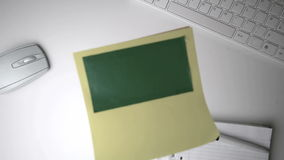 Yellow post it with green copy space falling on office desk Royalty Free Stock Image