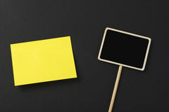Yellow post-its next to a square blackboard on a black background. Stock Images