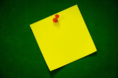 The yellow Post it leftwing. Post it forget the yellow on the green carpet. Red pin stock photography