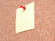 Yellow Post-it note. Yellow blank post-it note affixed to the corkboard with red pin Stock Image
