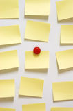 Yellow post it note and magnet button on whiteboard Royalty Free Stock Images