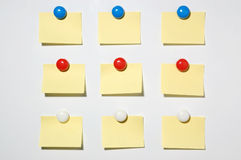 Yellow post it note and magnet button on whiteboard. 