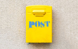 Yellow post office mailbox on plastered wall Stock Photo