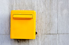 Yellow postbox. On the wall Stock Photo