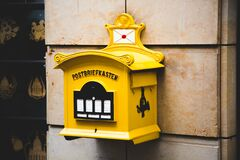 Yellow Postbriefkasten Floating Mailbox on Brown Concrete Wall Stock Photo