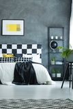 Black and white king-size bed. Yellow poster on concrete wall above black and white king-size bed next to shelf with black globe stock photography