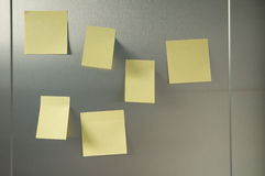 Yellow postit. Yellow pieces of paper to write things to do situated on fridge door royalty free stock images