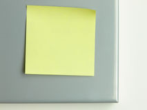 Yellow postit. Close up picture of a yellow postit on metal background Stock Photos