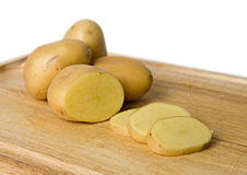 Yellow potatoes on board. Sliced and whole yellow potatoes on a wooden cutting board Stock Photos