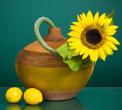 Yellow pottery vase with sunflower and two lemons Stock Image