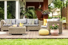 Yellow pouf and flowers next to rattan garden furniture on wooden terrace of house. Real photo stock images
