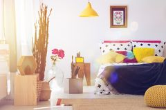 Mexican bedroom with yellow furniture. Yellow pouf and lamp in mexican bedroom with calavera skull poster, pink flowers, wooden stool and other furniture royalty free stock photography