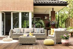 Yellow pouf on wooden patio. Yellow pouf next to a rattan armchair and flowers on wooden patio with striped pillows on sofa stock image