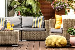 Yellow pouf on wooden terrace. Yellow pouf next to a rattan armchair on wooden terrace with striped pillows on sofa stock images