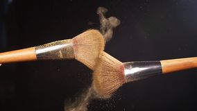 Yellow powder explosion with 2 beauty brushes. On a black background stock video footage