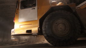 Yellow powerful dumper truck drives along underground tunnel stock video footage