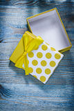 Yellow present box with bow on wooden board holidays concept Royalty Free Stock Photos