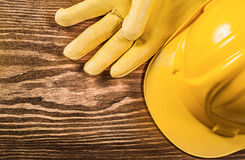 Yellow protective gloves building helmet on wooden board constru Stock Image