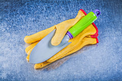 Yellow protective gloves stainless hand spade on metallic backgr Royalty Free Stock Photos