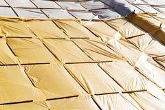 Yellow protective tarpaulins Stock Image