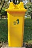 Yellow public bin in garden. Royalty Free Stock Photo
