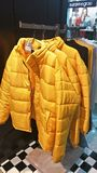 Yellow Puffer Jackets. Winter fashion, bright yellow puffer jackets on a rack at a store royalty free stock photography