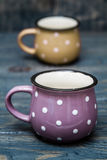 Yellow and Purple Ceramic Mug with White Dots on Blue Wooden Bac. Kground Stock Images