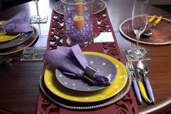 Yellow and Purple table place setting. Beautiful dining table setting for fun birthday, Thanksgiving, Christmas or special occasion with yellow and purple theme Stock Photo