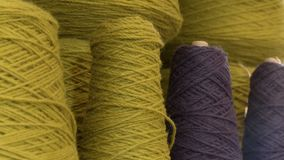 Yellow and purple threads for a loom. Cones of yellow and purple threads ready to be used on a loom stock video