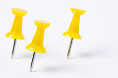 Yellow Pushpins on White Paper. Yellow Pushpins Isolated on White Background. Shallow Depth of Field Stock Image