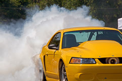 Yellow race car. Yellow car lost in smoke from its tires on a quick start Royalty Free Stock Image