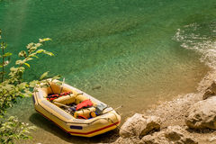Yellow raft on a riverbank. One seven-seater yellow raft with red safety vests and paddles on a riverbank in a canyon Royalty Free Stock Images