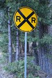 Yellow railroad crossing sign with pine tree background royalty free stock photography