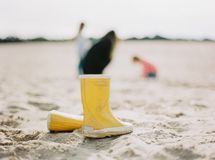 Yellow rain boots. Two yellow rain boots standing in the sand Stock Images