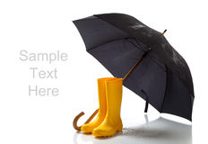 Yellow rainboots and black umbrella on white Stock Image