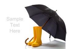 Yellow rainboots and black umbrella on white stock image