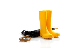 Yellow rainboots and black umbrella on white Royalty Free Stock Photo