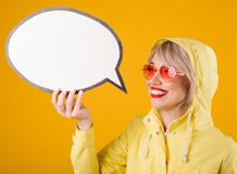 Yellow raincoat woman holding speech bubble. Bright emotions and yellow background. Pink heart shaped sunglasses royalty free stock photo