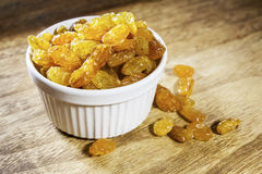 Yellow raisins or sultanas in a small white ceramic bowl Stock Image