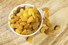 Yellow raisins or sultanas in a small white ceramic bowl Stock Images