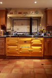 Yellow range oven in a lovely kitchen. A lovely large bright yellow traditional range oven on terracotta flooring, situated in a large country house. The oven Royalty Free Stock Photos