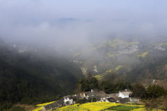 Yellow rape and villages on the hillside in spring, the mountain fog cover. Yellow rape and villages in the spring on the hillside, hill, road and village Royalty Free Stock Images