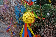 Yellow rattan ball hanging on a Christmas tree with ribbons on background of christmas garland. At Russian national festival `Shrove` in Moscow stock photo