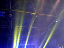 Yellow rays of spotlights in the club. royalty free stock image